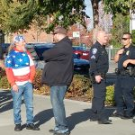 A long-haired older white male Patriot Prayer rallier dressed in an American flag jacket and bandana talks with a skeptical counter protestor while 2 Tacoma police keep watch.