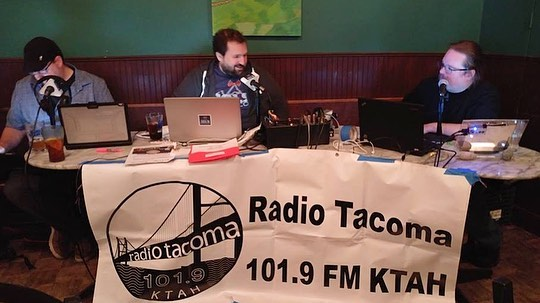 Josh, Morgan, Sam sitting behind a Radio Tacoma 101.9 KTAH banner at a long table using laptops and speaking into microphones